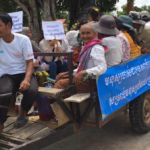 Photo of elderly women holding up signs for an elderly rights awareness campaign. They are on top of a tractor truck.